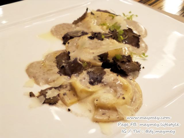 Homemade ravioli filled with Burrata cheese on parmesan cream and black truffle